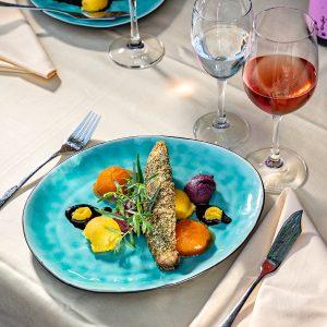 Das Bild zeigt einen fein gedeckten Tisch und ein Fischgericht.