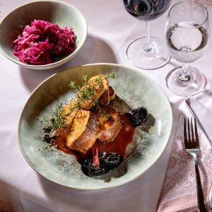 Das Bild zeigt einen fein gedeckten Tisch und ein Fleischgericht.