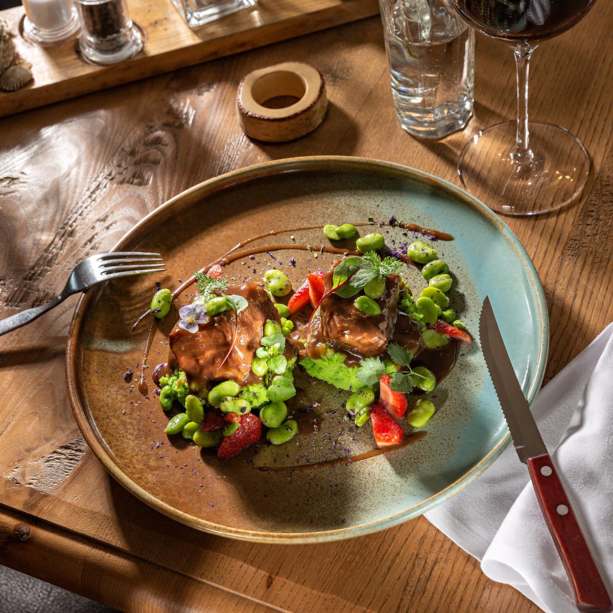 Das Bild zeigt einen rustikalen Tisch und ein Fleischgericht.