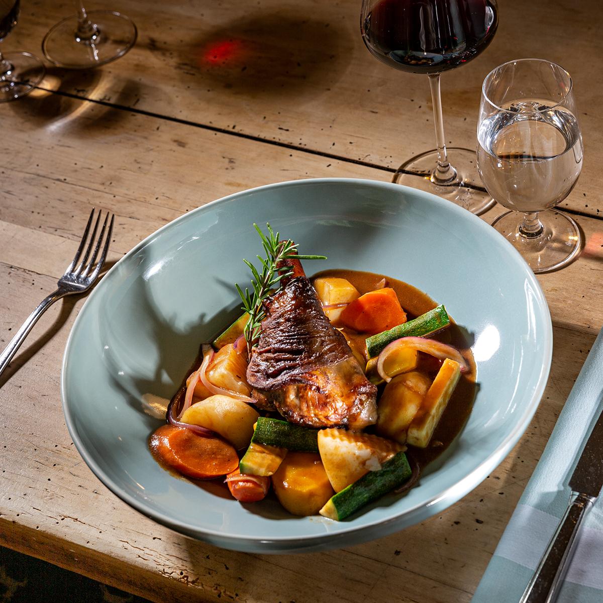 Das Bild zeigt einen Holztisch und ein Fleischgericht mit viel Gemüse.