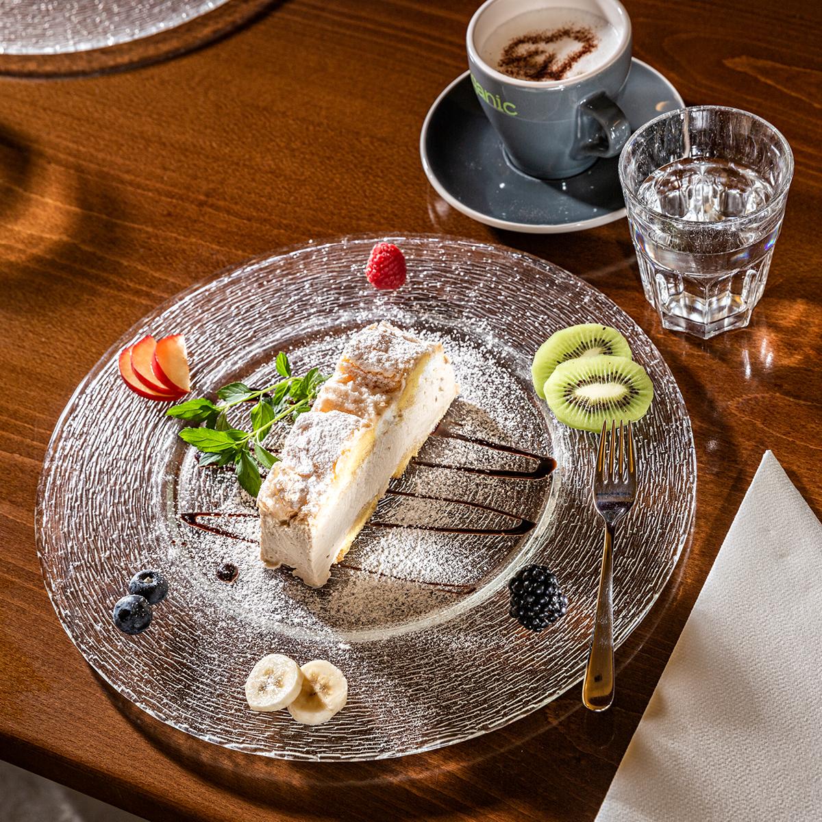 Das Bild zeigt eine schön garnierte Cremeschnitte mit einer Kaffeetasse daneben.