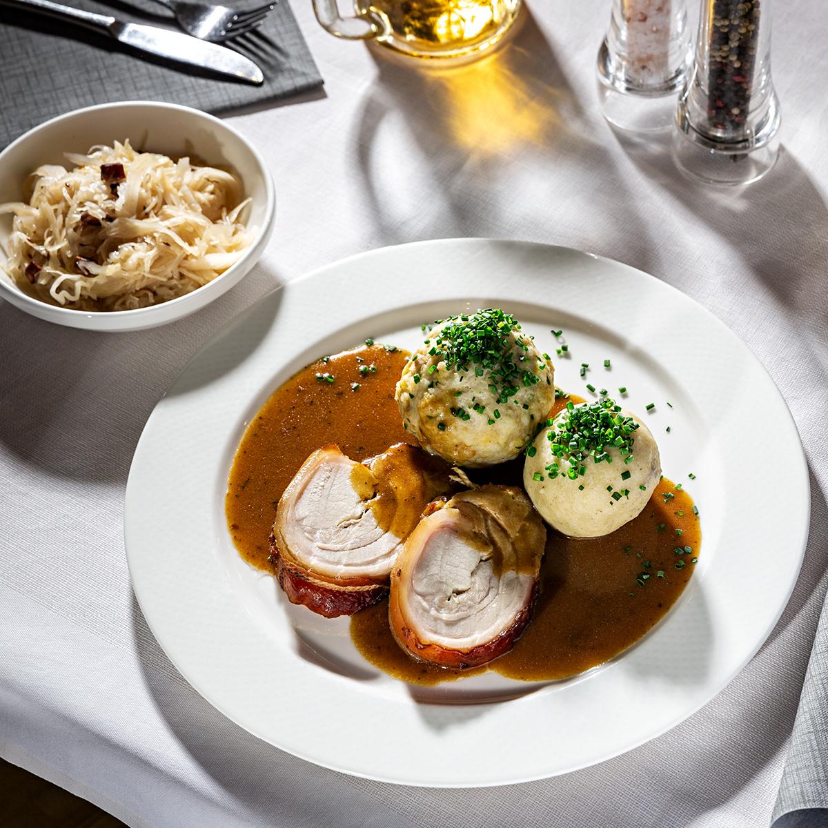 Das Bild zeigt ein leckeres Fleischgericht mit Semmelknödeln und Sauerkraut.