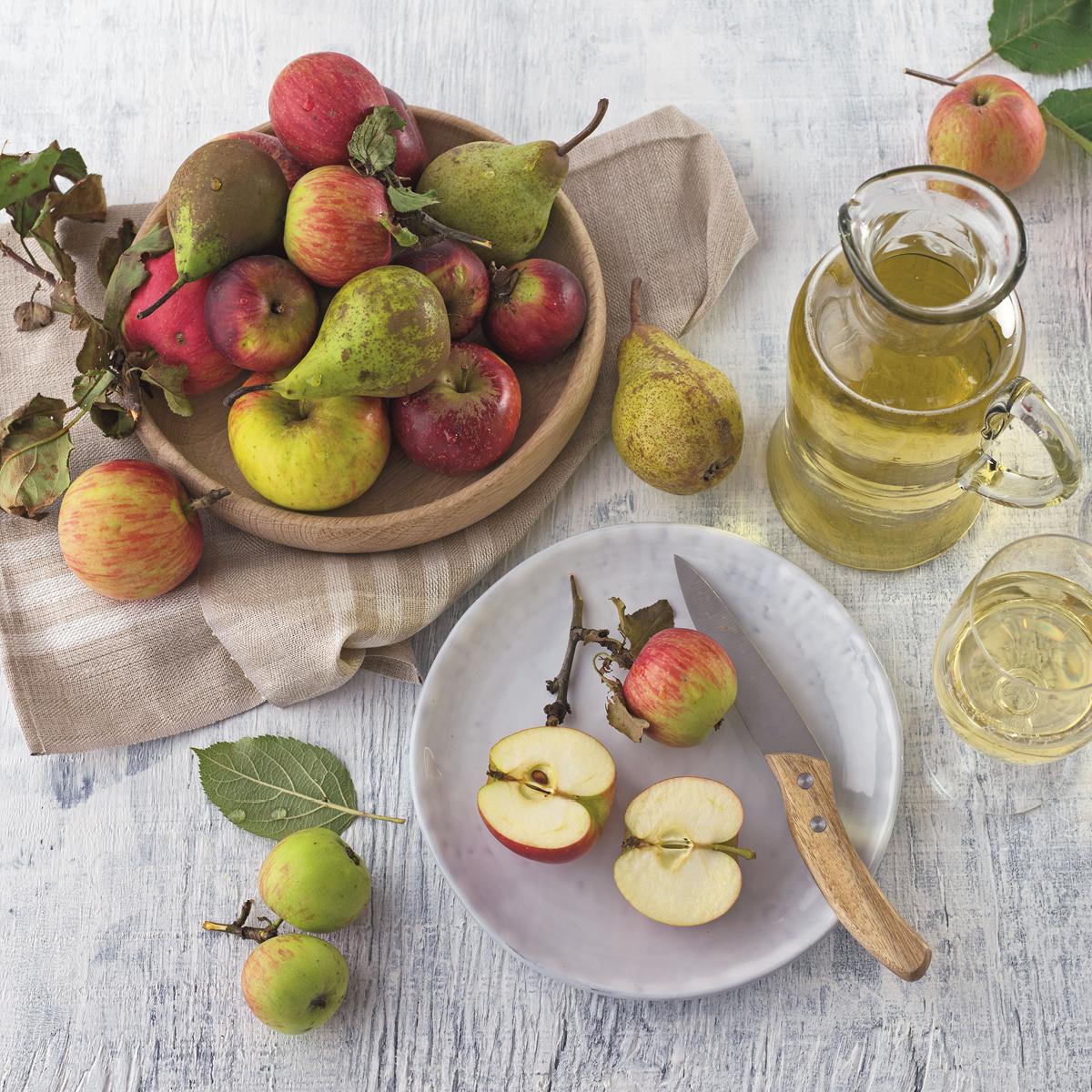 Das Bild zeigt einen Tisch mit Obst und einer Karaffe mit Saft.