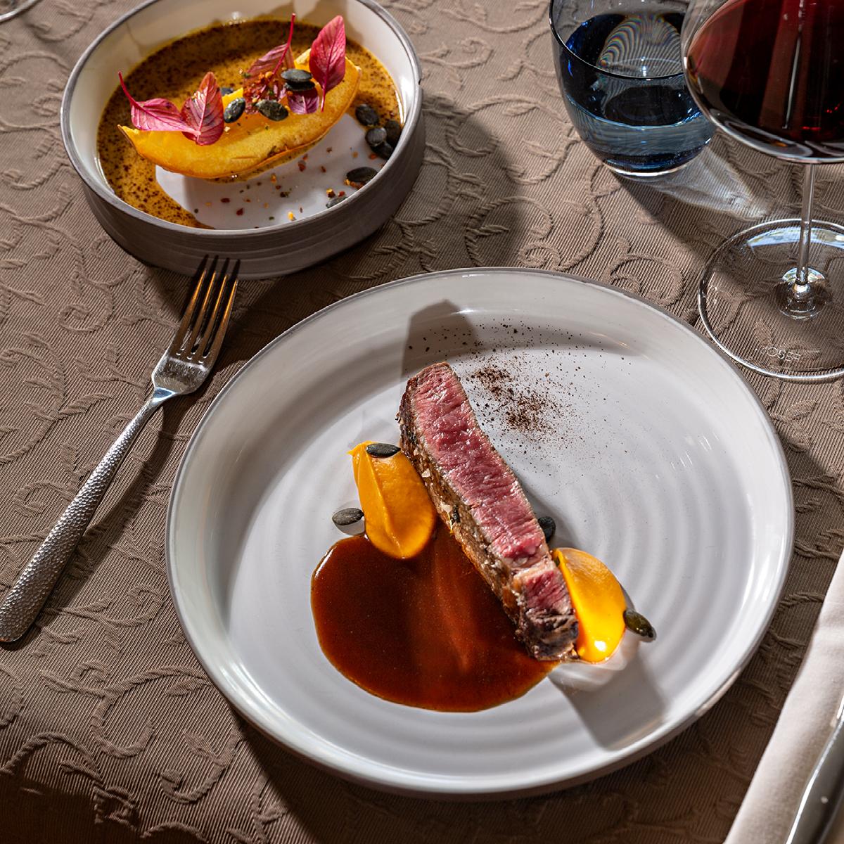 Das Bild zeigt ein köstliches Fleischgericht mit Beilagen und einem Rotweinglas daneben.