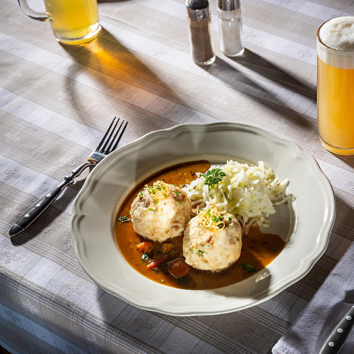 Das Bild zeigt ein appetitliches Fleischgericht mit Semmelknödeln und Kraut.