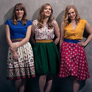 Das Bild zeigt die Poxrucker Sisters, drei bunt gekleidete Schwestern aus dem Mühlviertel.