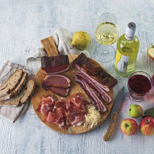 Das Bild zeigt eine kalte Jausenplatte mit Obst, Brot, Fleisch und einer Weinflasche.