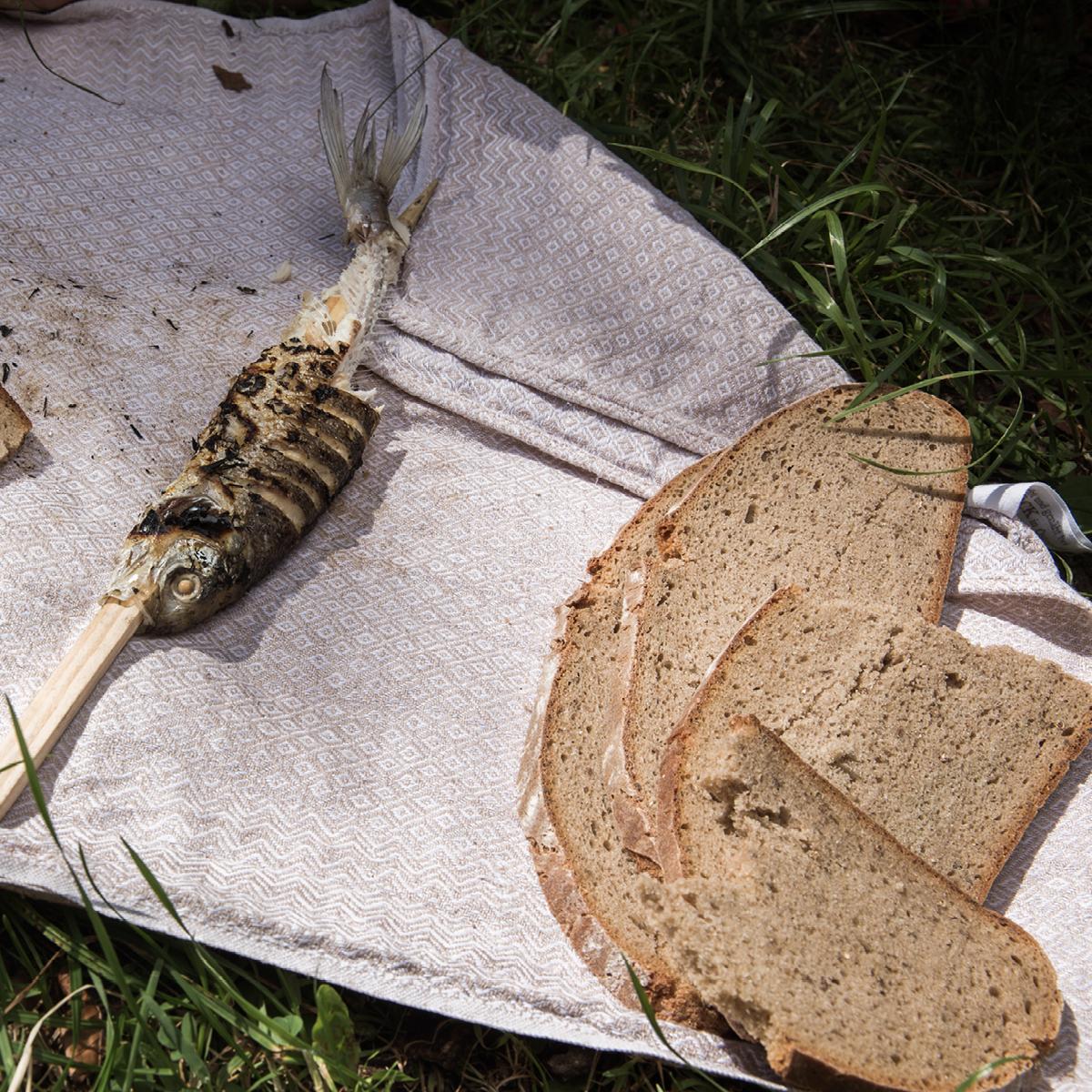 Das Bild zeigt einige Scheiben Brot und einen kleinen Steckerlfisch.