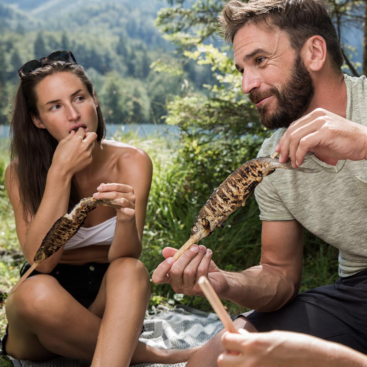 Das Bild zeigt einen Mann und eine Frau, die sich an einem Seeufer ihre Steckerlfische schmecken lassen.