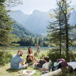 Das Bild zeigt eine kleine Gruppe junger Menschen, die sich am Seeufer entspannen.