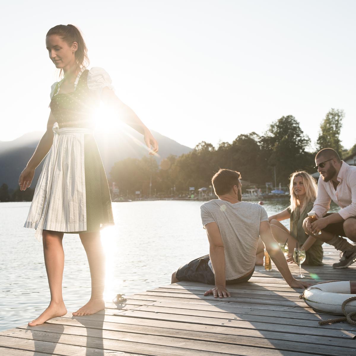 Das Bild zeigt eine Gruppe junger Menschen auf einem Steg, der in einen See reicht.