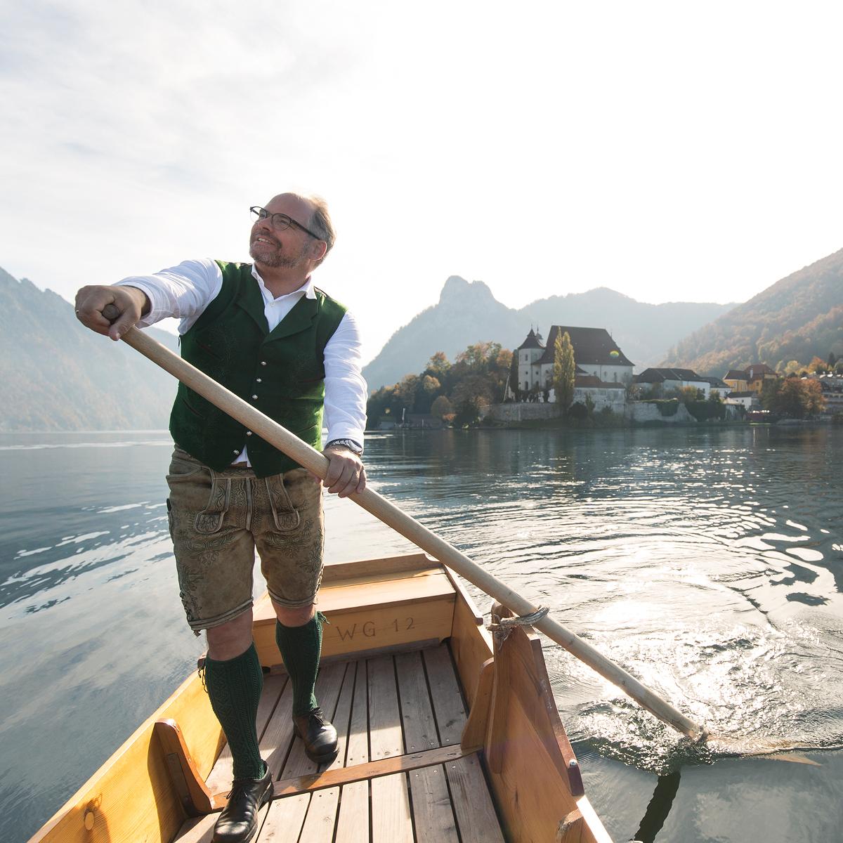 Das Bild zeigt einen Mann in Tracht, der über einen See rudert.
