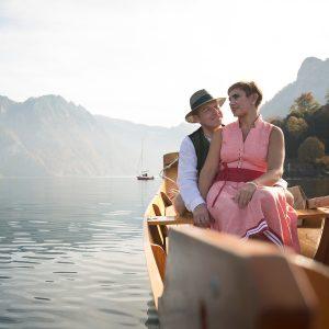 Das Bild zeigt ein Paar, das über einen See gerudert wird.