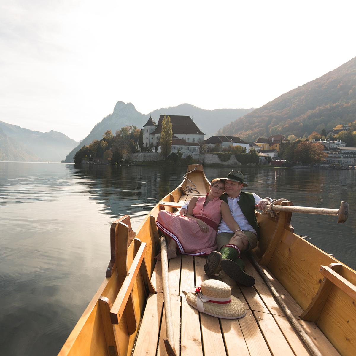Das Bild zeigt ein liegendes Paar in einem Boot, das über einen See gleitet.