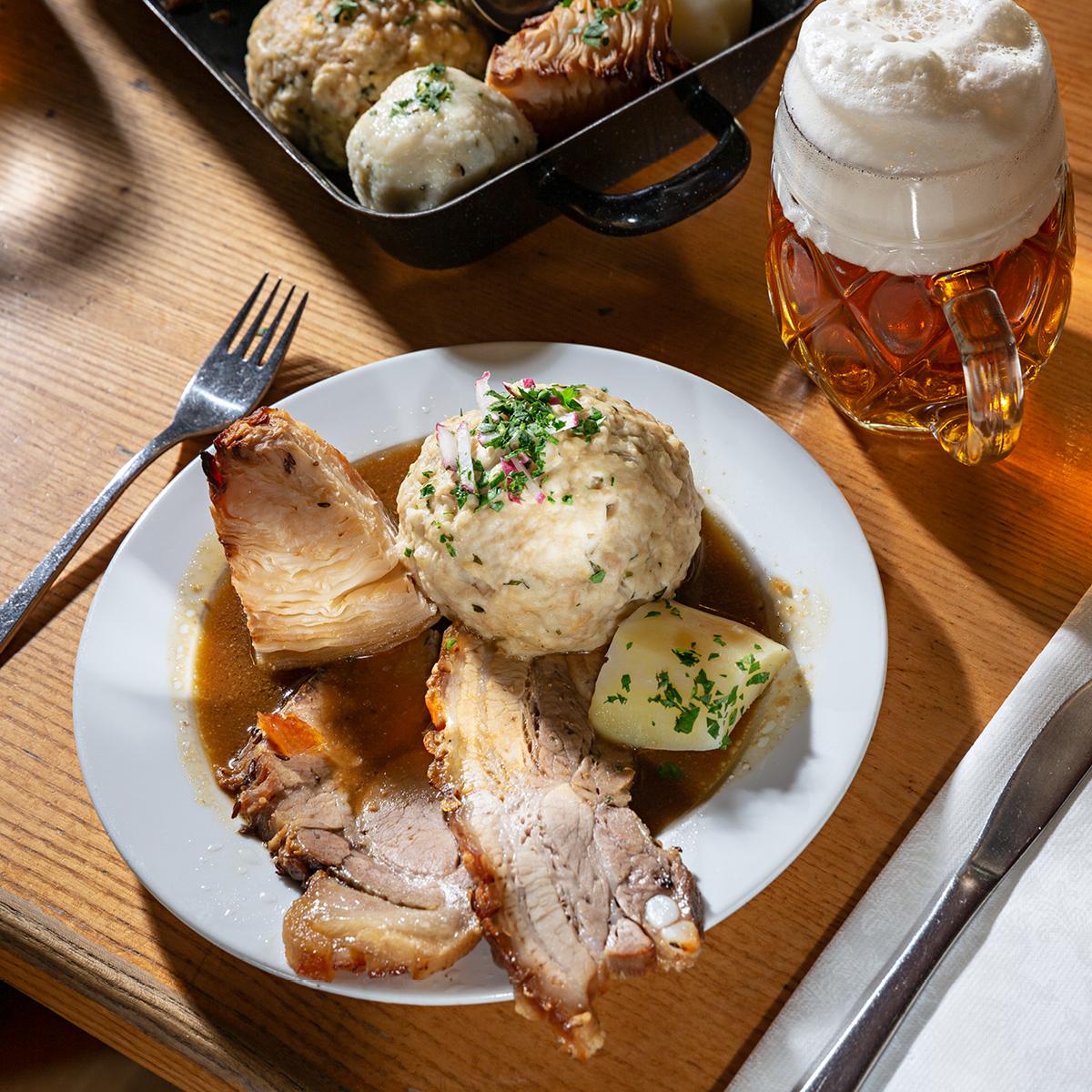 Das Bild zeigt ein köstliches Fleischgericht mit Beilagen und einem Bierglas daneben.