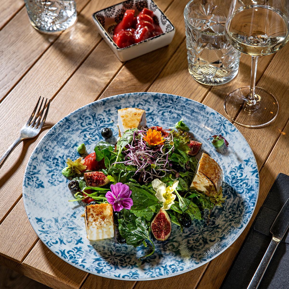 Das Bild zeigt einen knackig-frischen Salat auf einem Holztisch.