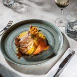 Das Bild zeigt ein schmackhaftes Fleischgericht auf einer feinen Tischplatte.