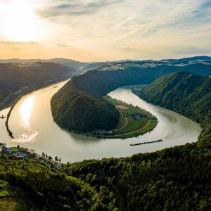 Das Bild zeigt die Donauschlinge von oben bei Sonnenuntergang.